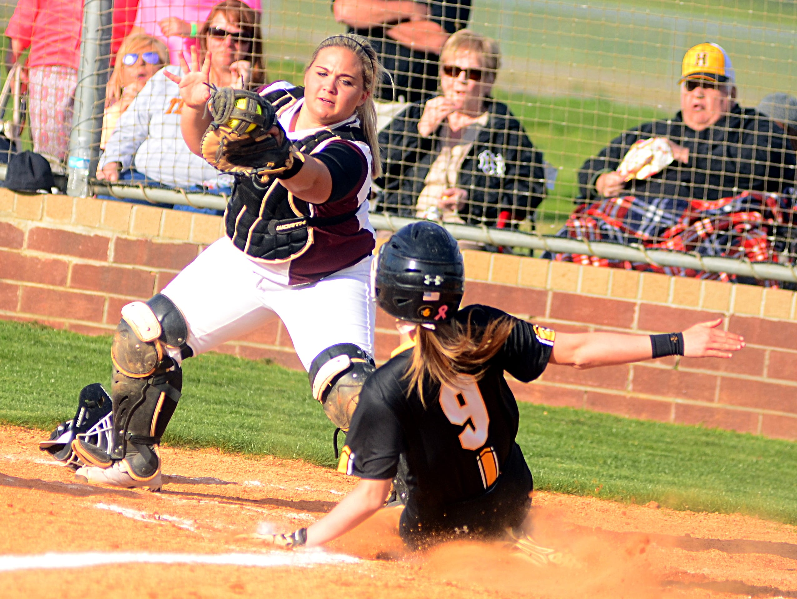 Station Camp High senior catcher Chasity Wheeley receives a throw at home plate as Hendersonville junior M.J. Mattei scores during first-inning action.