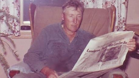 Ken Corey reads paper after a long day on the farm.