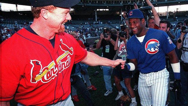 Mark McGwire, left, and Sammy Sosa shake hands before a game in 1998.