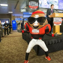 Phoenix Mayor Greg Stanton speaks at the unveiling of the Super Bowl XLIX countdown clock while mascot Spike looks at the crowd at Phoenix Sky Harbor International Airport on Aug. 6, 2014..