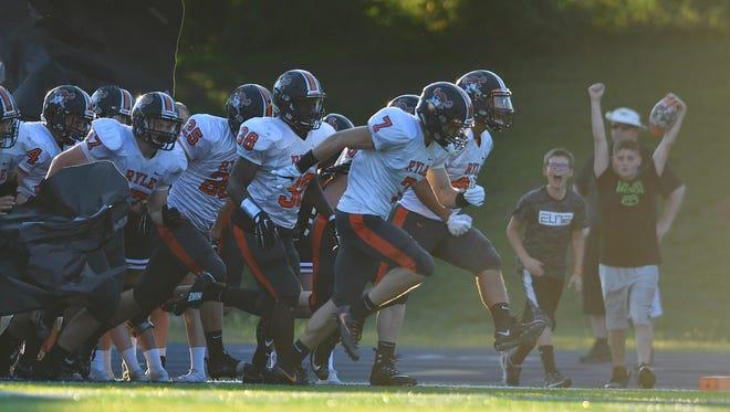 The Ryle Raiders take the field before facing off against Covington Catholic Friday, Aug. 18, at Covington Catholic High School.