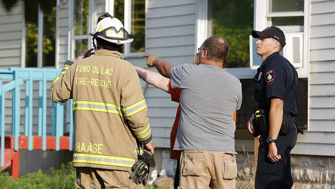 Bystanders talk to members of the Fond du Lac Fire/Rescue following a house fire at 111 W. McWilliams St. on Wednesday night.