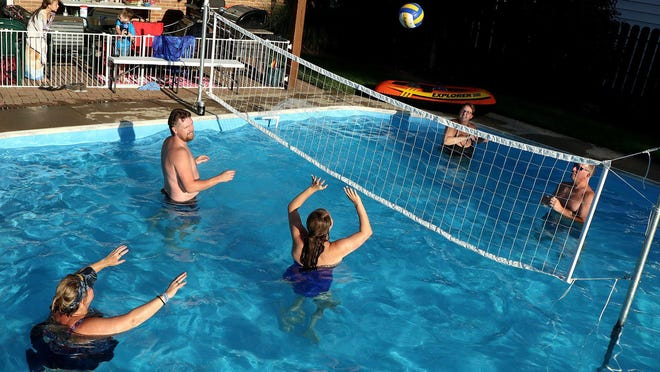 Gina Burnside plays volleyball with her neighbors in her swimming pool at her Hilltop home, which she rents out via the Simply app. From left: Dawn Weimer; Chris Freeman; his wife, Brittany Freeman; Gina Burnside; and Dawn's husband, Robert Weimer.