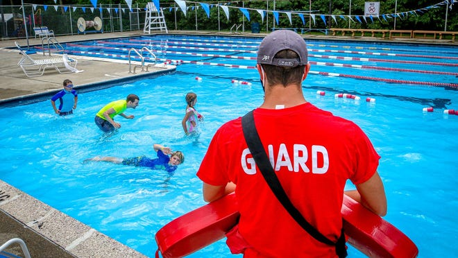 Camp instructor Jason Spencer, in yellow, helps children enjoy the pool at the Bayside Family YMCA in Barrington.
