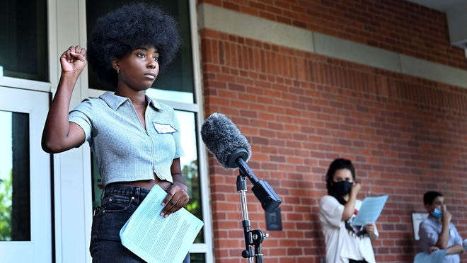 """Laila Christian, 18, raises her fist after reading a passage from Frederick Douglass' 1852 speech, """"What to the Slave is the Fourth of July,"""" Thursday evening on the steps of the Morse Institute Library in Natick. About a dozen Natick teenagers read from the speech. Christian graduated from Natick High School last month."""