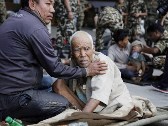 A Nepalese man attends to an elderly as victims of Saturdayís earthquake, wait for ambulances after being evacuated at the airport in Kathmandu, Nepal, Monday, April 27, 2015. The death toll from Nepal's earthquake is expected to rise depended largely on the condition of vulnerable mountain villages that rescue workers were still struggling to reach two days after the disaster.