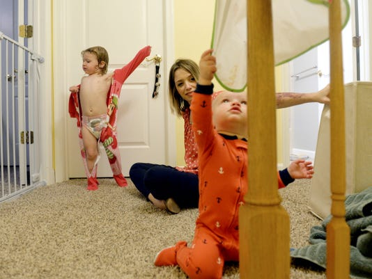 """Meagan Feeser, center, watches as her son GB, 1, yanks on a paint-covered smock hanging on the banister while daughter Holden, 2, puts on her pajamas at Feeser's West Manchester Township home. Feeser, who works full-time for Downtown Inc., began her Oh, Bother blog in March 2013. Describing herself as a """"DIYer wannabe,"""" Feeser is one of several local parents who use social media to connect with other parents."""