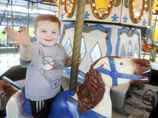 Kyler Beaverson, 2, of Jacobus takes a ride on the merry-go-round during Saturday's Fan Fest at Santander Stadium.