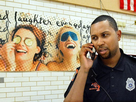 York High school police officer Quinn Johnson keeps in touch with the other school officer taking a cell phone call in the cafeteria Friday, April 17, 2015. He also uses a district radio and county radio to communicate. Johnson says he wants to provide a mentor and father figure to students at the school. Bill Kalina -bkalina@yorkdispatch.com