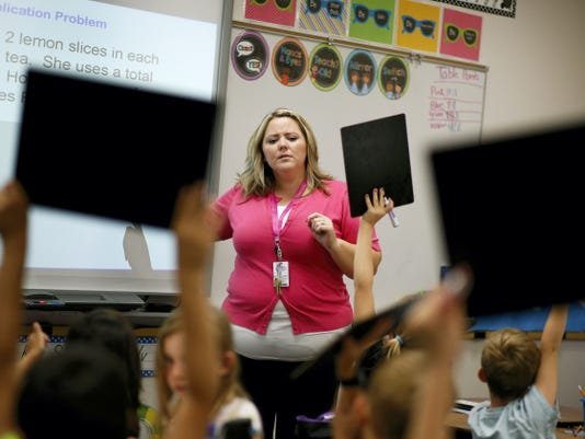 In this Sept. 10, 2015, photo, Tia Martin teaches a third-grade class at Ulis Elementary School in Henderson, Nev. Martin is a long-term substitute teacher who is taking an alternative route to licensure program to get a regular teaching license. After years of recession-related layoffs and hiring freezes, school systems in pockets across the United States are in urgent need of more qualified teachers and students, instead of meeting their new teacher on their first day of class, are finding a substitute. (AP Photo/John Locher)<br>
