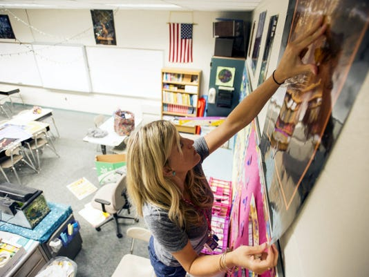 Megan Dodson, an English learning support teacher at Cedar Crest Middle School, hangs a poster in her classroom for the upcoming 2015-16 school year on Aug. 12. Cedar Crest students return to classes on Aug. 31.