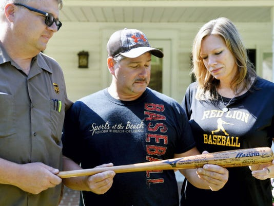 UPS driver Hans Engelman, and Glenn and Tina Hill, hold a Mizuno maple baseball bat signed by more than 60 of their son Stone's former teammates. Engelman collected the signatures during the past month and delivered the bat to Stone's family as a surprise on Thursday.