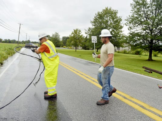 Met-Ed lead lineman John Stover, right, and first-class lineman Chris Hied remove a downed electrical wire from Canal Road between Bull Road and Lewisberry Road in Conewago Township after a strong storm passed through Thursday.