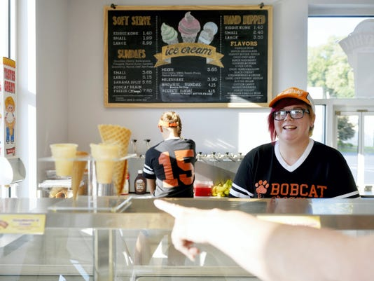 Northeastern senior Jasmine White, 17, right, takes a customer's ice cream order as fellow senior Kyleigh Smeltzer, 17, works behind the counter Friday at Bobcat Creamery in Manchester.