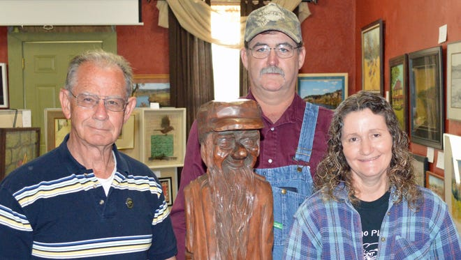"""Calico Rock Museum trustee Wayne Wood (from left) joins Kenny and Sue Stapleton in honoring her father, Junior Cobb, for his amazing artistic talents along with """"Winking Zeke"""" a wood carving Cobb did for Wood's birthday in 1972."""