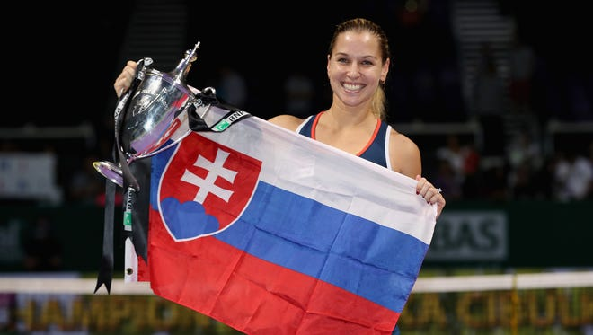 Dominika Cibulkova of Slovakia poses with the trophy after victory in her singles final against Angelique Kerber at the BNP Paribas WTA Finals Singapore at Singapore Sports Hub.