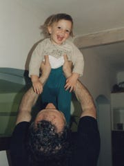 Mark Roser lifts his youngest son, Ethan Roser, up in the air.