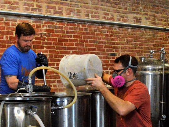 Ryan DeKok adds grain during the mashing process at Red Gap Brewing Co., while Jason Mahon watches.