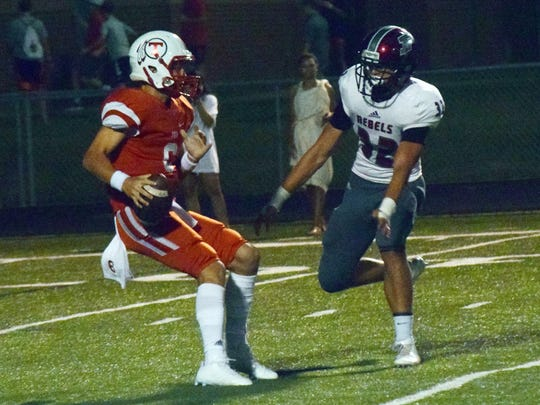 Tioga quarterback Blake McGehee (6) avoids a sack from a Pineville defender during the 2017 game between the two schools.