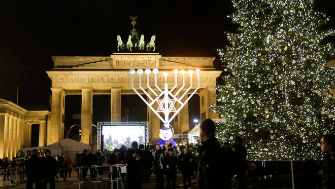 In this Dec. 27, 2016, file photo, a giant Hanukkah menorah, center, set up by the Jewish Chabad Educational Center, is illuminated at the Pariser Platz in front of the Brandenburg Gate in Berlin. Menorah lightings are planned there again this year for Hanukkah, which begins Tuesday, and at other landmarks and destinations around the world.