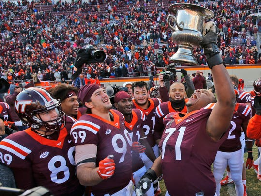 FILE - In this Saturday, Nov. 26, 2016, file photo, Virginia Tech offensive lineman Jonathan McLaughlin (71) celebrates with Commonwealth Cup as defensive lineman Vinny Mihota (99) joins in after their 52-10 win over Virginia in an NCAA college football game in Blacksburg, Va. The trophies could be the only prizes for the winners in several games during championship weekend. This is not the NCAA basketball tournament. Those titles don't automatically come with playoff spots and in some cases the wrong winner could ruin things for a conference. (AP Photo/Steve Helber, File)