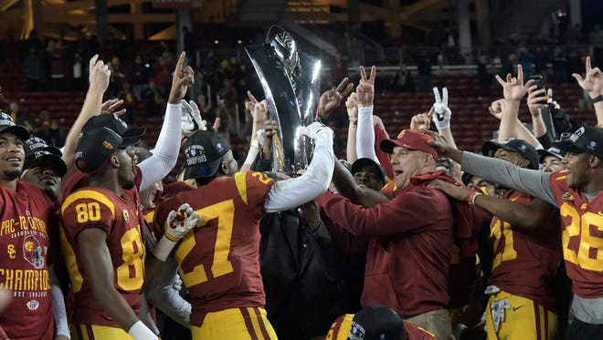 Dec 1, 2017; Santa Clara, CA, USA; Southern California Trojans players and coach Clay Helton hoist the championship trophy after the Pac-12 Conference championship game against the Stanford Cardinal at Levi's Stadium. USC defeated Stanford 31-28 Mandatory Credit: Kirby Lee-USA TODAY Sports