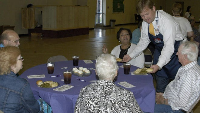Horizon Medical Center CEO Dustin Greene (standing) serves meals to cancer survivors and friends Thursday evening at First Baptist Church.