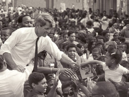 Sen. Robert Kennedy clasps the hand of an unidentified