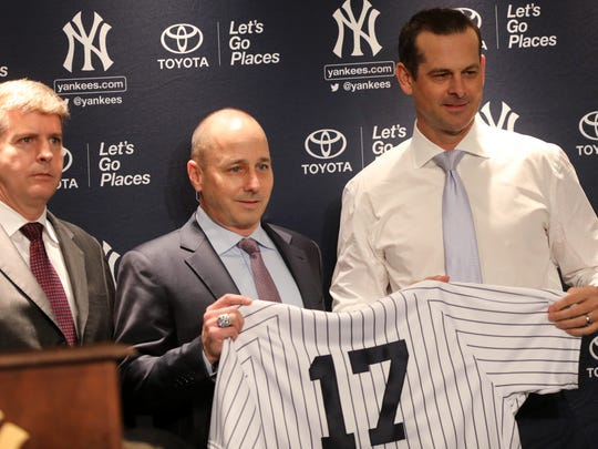 Hal Steinbrenner, Brian Cashman pose with Aaron Boone