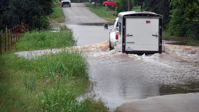 In this file photo, a pickup pulling a trailer makes its way through about 10-inches of water over Haws Road near Horseshoe Bend Estates after flooding. An Iowa Park couple is claiming their neighbor's actions affected a nearby creek causing it to flood even after moderate rainfall.