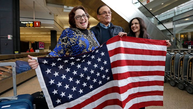 Jayne Novak, left, of Silverdale smiles as she stands with husband Allen Novak, newly arrived from Iran, and his daughter, Nikta, as they stand with a flag Monday, at Seattle-Tacoma International Airport. Allen and Nikta were stopped twice last week because of the travel restrictions ordered by President Donald Trump.