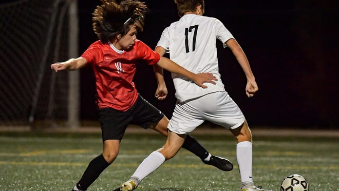 Shawnee Heights senior Johnny Jasso, left, battles Lansing's Carter Whitlow for the ball during Tuesday's Class 5A soccer quarterfinal at the Bettis Family Sports Complex. The T-Birds advanced to the 5A semifinals with a 2-1 win over the Lions.