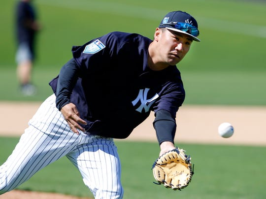 New York Yankees starting pitcher Masahiro Tanaka (19) fields the ball during spring training workouts at George M. Steinbrenner Field.