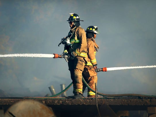 Memphis fire fighters keep an eye on the smoking remains