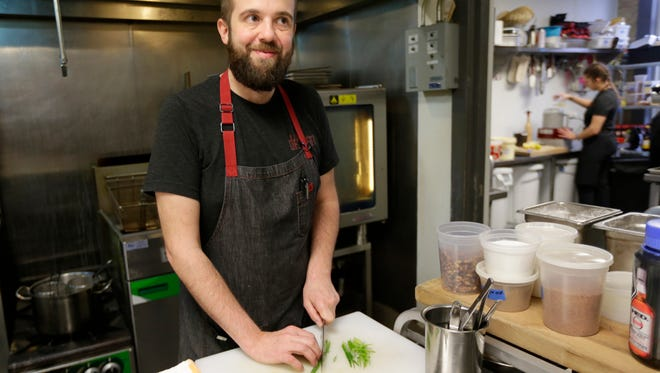 Dan Jacobs, a chef-owner at Dandan, cuts scallions at the restaurant. Jacobs, whose cooking in Milwaukee has won critical acclaim, these days often needs help opening jars in the kitchen because of Kennedy's disease, an inherited neuromuscular ailment.