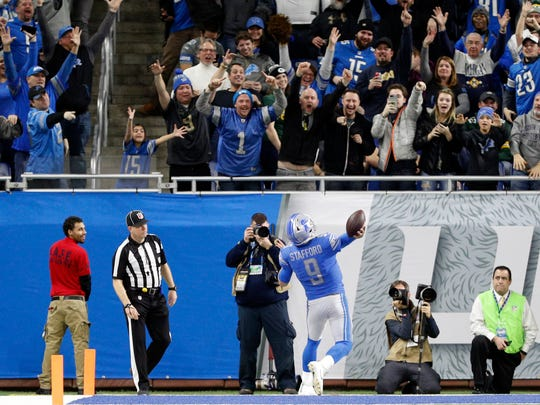 Matthew Stafford throws the ball into the Ford Field crowd after catching a two-point conversion against the Packers on Dec 31, 2017.