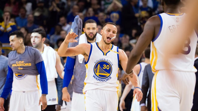Golden State Warriors guard Stephen Curry (30) celebrates with forward Draymond Green (23) as a timeout is call against the Boston Celtics during the second quarter at Oracle Arena.