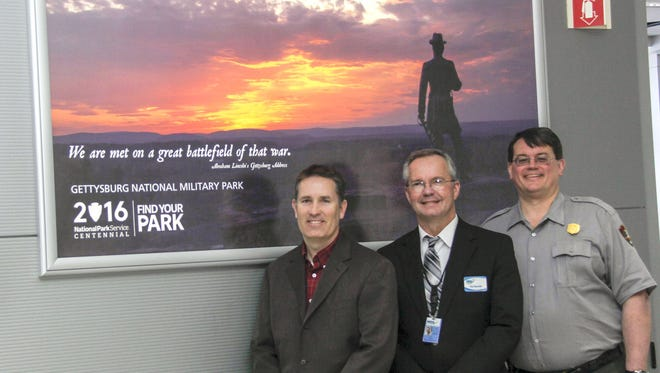 Employees of Harrisburg International Airport and Gettysburg and Eisenhower Parks are shown in front of a new display ad at Harrisburg International Airport. Pictured, from left, are: Scott Miller, public relations deputy director of Harrisburg International Airport; Timothy Edwards, executive director of Harrisburg International Airport; and Ed W. Clark, superintendent of Gettysburg National Military Park and Eisenhower National Historic Site.