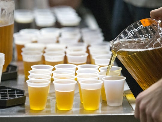 Beer being poured into sample cups at Sun King Brewing.
