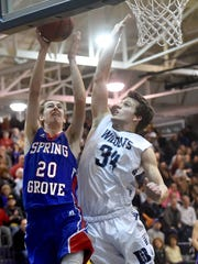 Spring Grove's Drew Gordon goes up and scores against Dallastown's Ben Ward during the Rockets' 62-58 victory on Tuesday, Jan. 31, 2017.