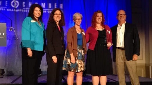 New Leaf Market accepts the 2014 Business of the Year award at today's luncheon. Pictured here are Lisa Elam, left, of Capital City Bank, Tallahassee Democrat Publisher Julie Moreno, New Leaf board President June Wiaz, New Leaf marketing and projects manager Cristin Burns, and Chamber Chairman Ed Murray Jr.