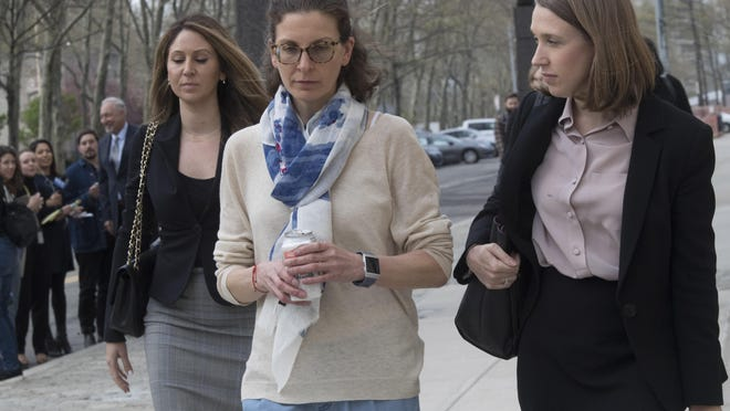 Clare Bronfman, center, leaves Federal court in the Brooklyn borough of New York, Friday, April 19, 2019. Bronfman has pleaded guilty to charges implicating her in a sex-trafficking conspiracy case against an upstate New York self-help group.