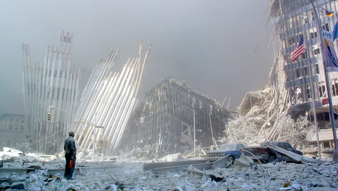 A man stands in the rubble Sept. 11, 2001, after the collapse of the first World Trade Center tower in New York.