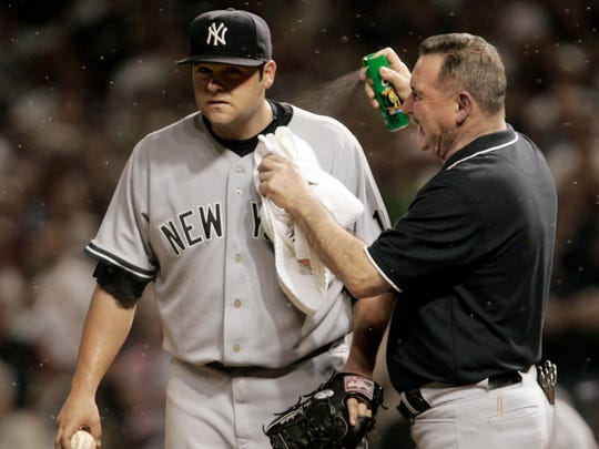 New York Yankee head trainer Gene Monahan sprays New York Yankees pitcher Joba Chamberlain with bug spray as swarms of small insects swarm in the eighth inning of Game 2 of an American League Division Series baseball game agianst the Cleveland Indians Friday, Oct. 5, 2007, in Cleveland.