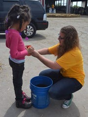 Waupun FFA President Mykayla Kuhn helps an elementary student fill her cup with potting mix at the Horticulture station at the Waupun FFA Day On the Farm program.