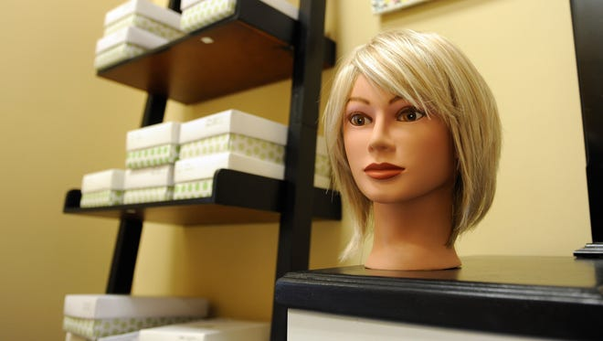 The Francesca style wig in light blonde on the vanity table near a bookcase holding different styles of wigs for cancer patients.