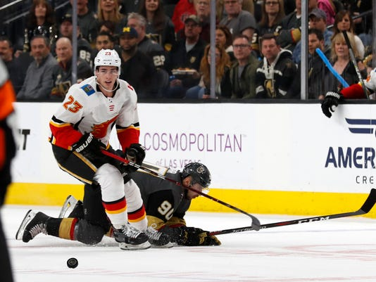 Calgary Flames center Sean Monahan (23) chases the puck as Vegas Golden Knights left wing Tomas Tatar (90) falls during an NHL hockey game Sunday, March 18, 2018, in Las Vegas. (AP Photo/Steve Marcus)