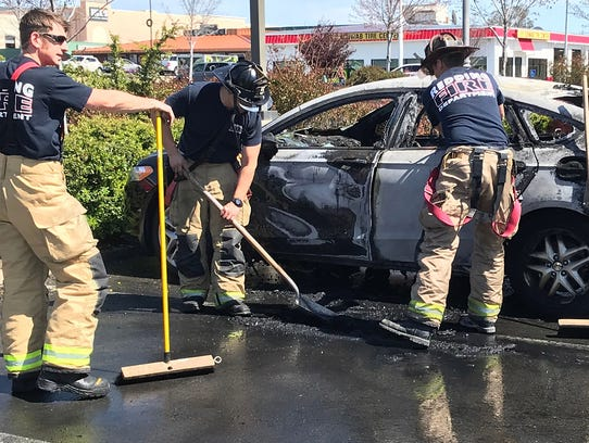 Firefighters clean up after two parked cars caught