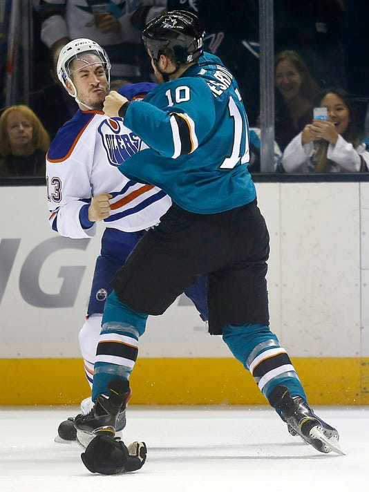 Edmonton Oilers right wing Steve Pinizzotto (13) and San Jose Sharks center Andrew Desjardins (10) fight during the first period of an NHL hockey game Tuesday, Dec. 9, 2014, in San Jose, Calif. (AP Photo/Tony Avelar)