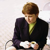 High angle view of a businesswoman holding a cup of coffee looking at a laptop